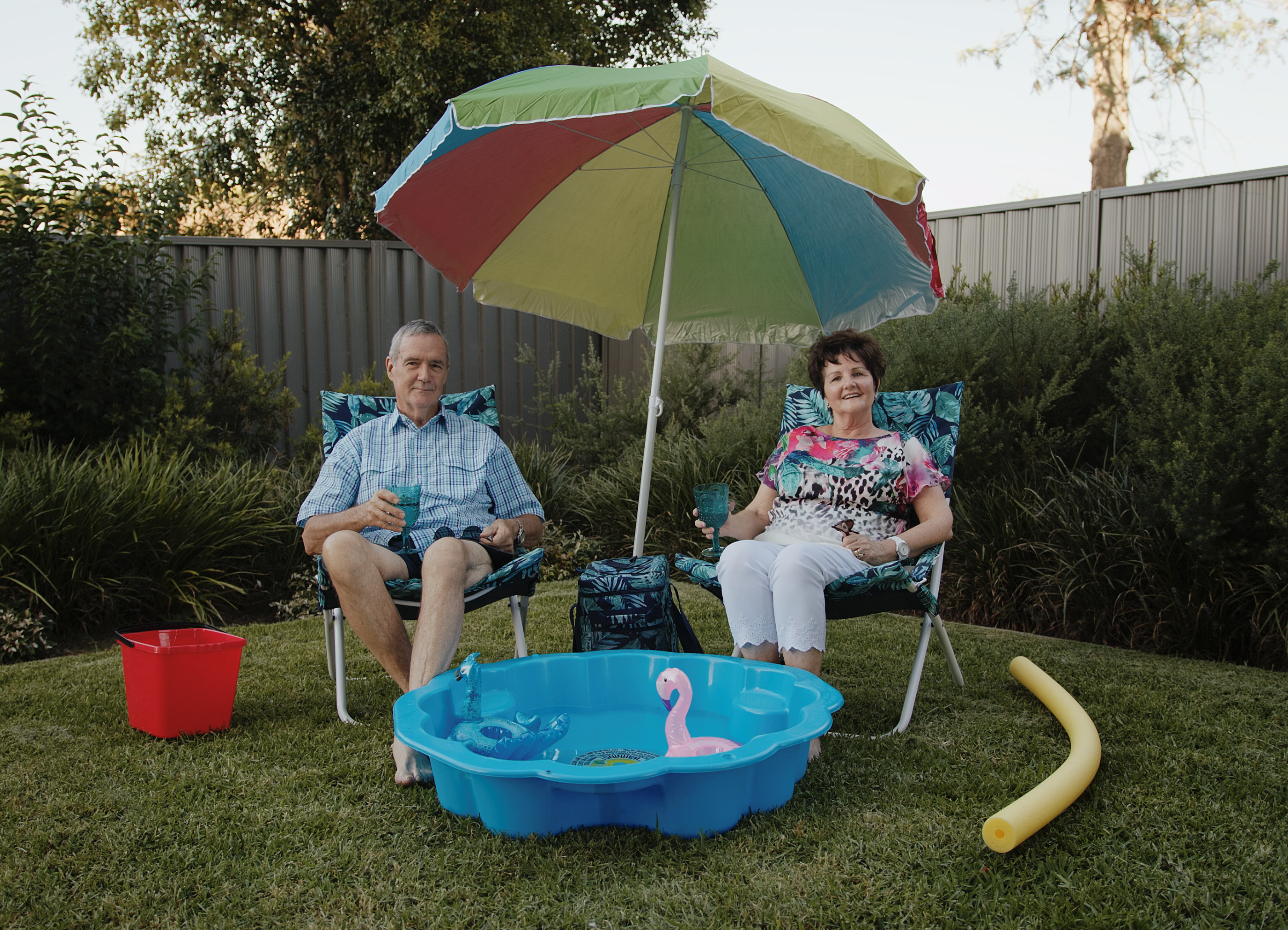 A photo of an elderly couple sitting next to a portable pool