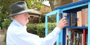 A side-on view of John as he reaches into a blue street library, placing two books. He is wearing a light blue, long-sleeved shirt and a navy, wide brimmed hat.