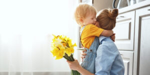 Young boy hugging a woman who is holding yellow flowers and is facing away