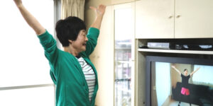 Elderly Asian woman copying exercise video on television