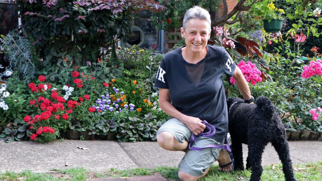 Kaye couched down looking at the camera with her black Labradoodle faced away and her shared garden in the background