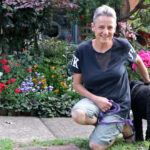 Kaye couched down looking at the camera with her black Labradoodle Cecil faced away and her shared garden in the background
